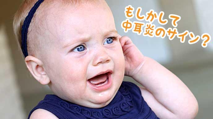 泣きながら耳を触る赤ちゃん