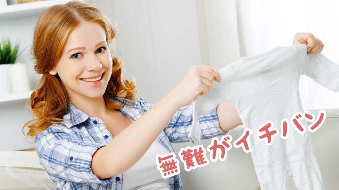 笑顔で赤ちゃん用の服を広げる母親