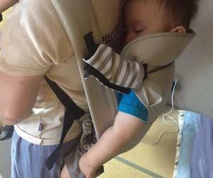 おんぶ紐で親の背中で眠る赤ちゃん