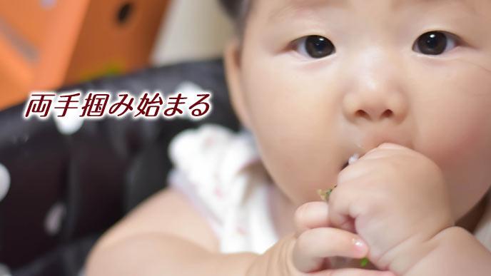 両手つかみで食事する赤ちゃん