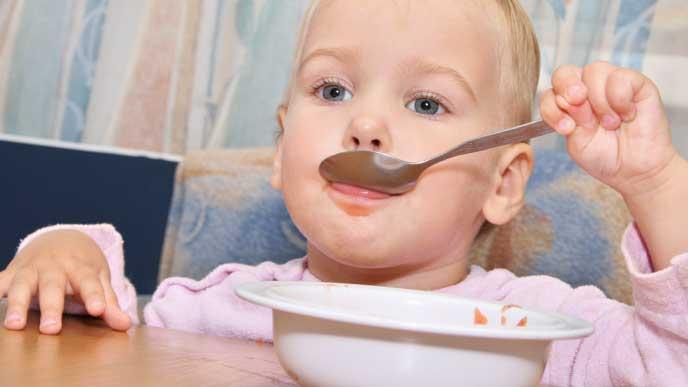 スプーンでご飯を食べる赤ちゃん