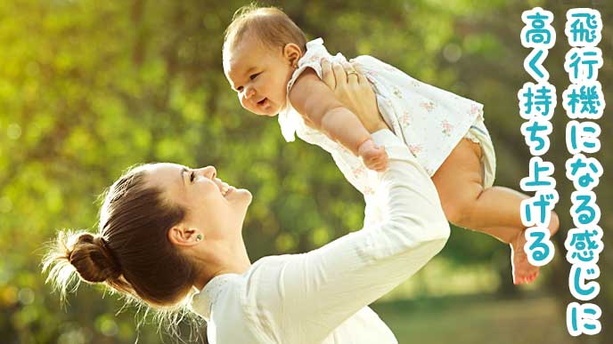 赤ちゃんを高く持ち上げるママ