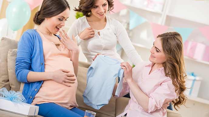 友達からベビー服を贈られる妊婦