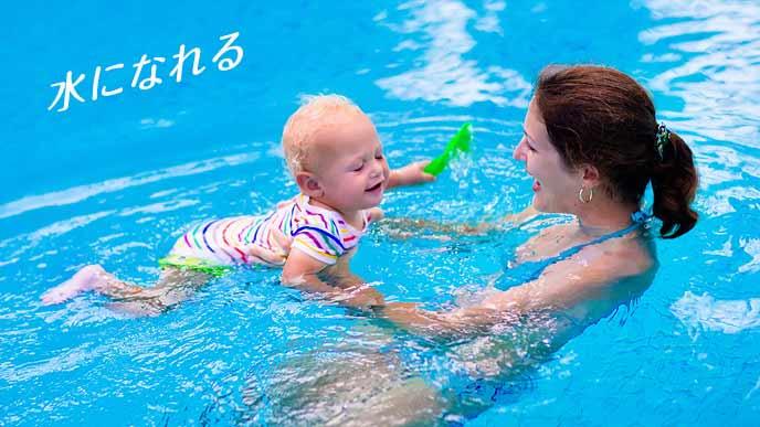 プールで母親に掴まれて遊ぶ赤ちゃん