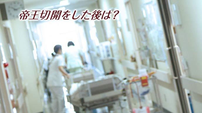 病院の廊下を看護師に運ばれるベッド