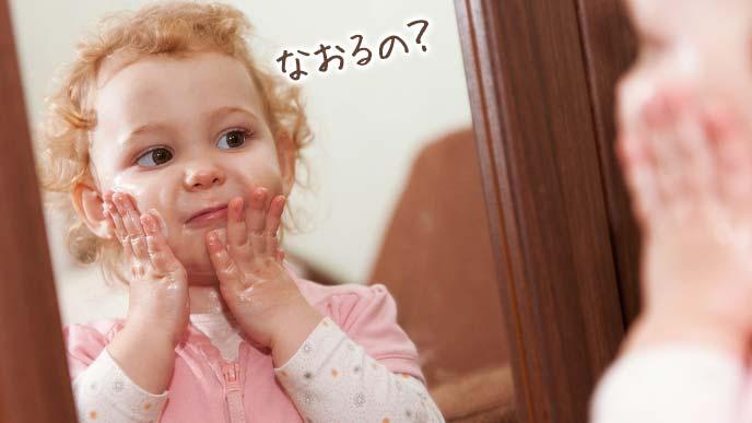 鏡で自分のくせ毛を見つめる幼児