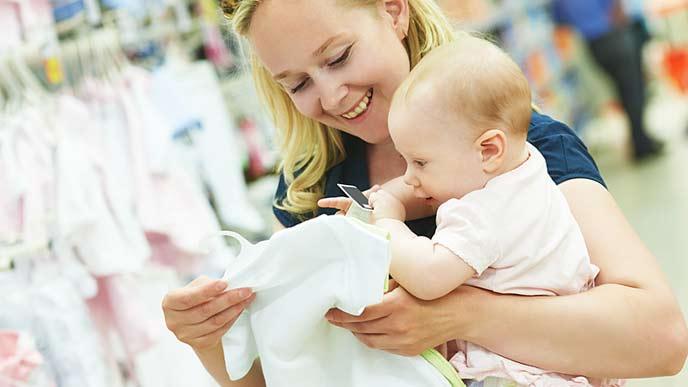 赤ちゃんを抱いてベビー服を手に取る母親