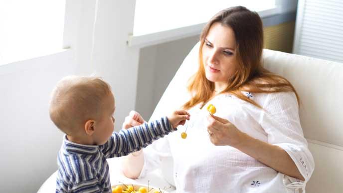 子供と一緒にサクランボを食べる妊婦
