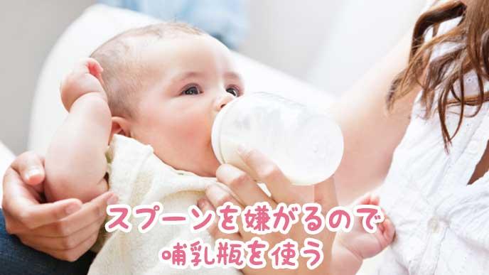 哺乳瓶を口にくわえる赤ちゃん