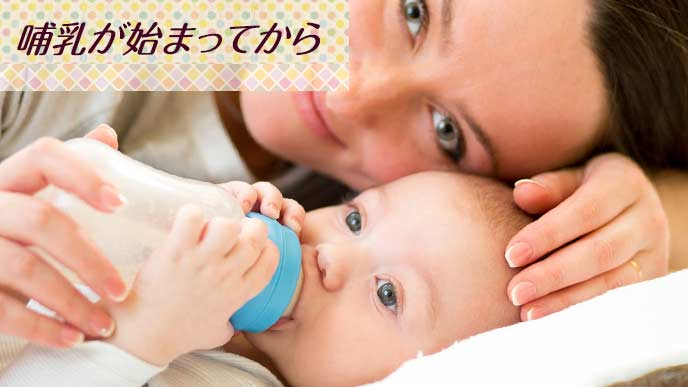 赤ちゃんに哺乳瓶でミルクを飲ませる母親
