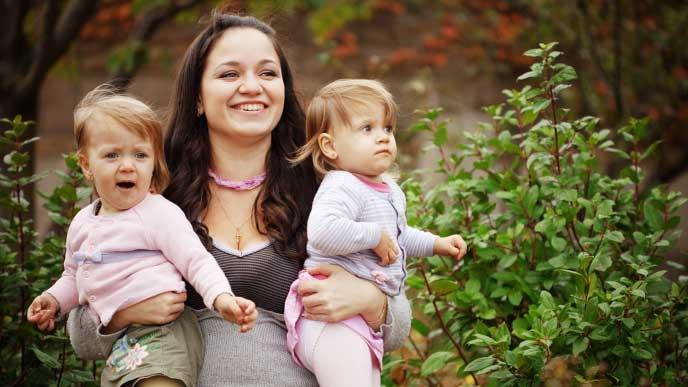 双子の赤ちゃんを抱きかかえる母親