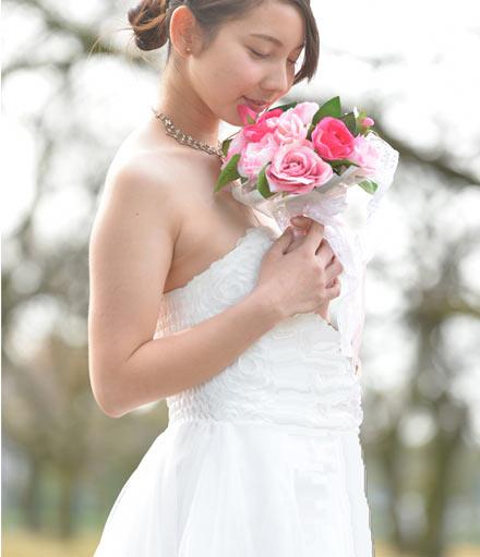 ドレスを着てバラの花を持つ妊婦の花嫁