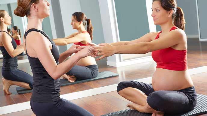 マットの上に座りストレッチする妊婦