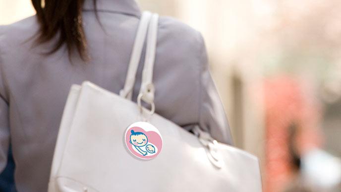 ショルダーバッグにマタニティマークを付ける女性