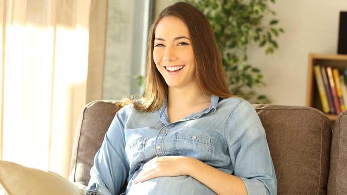 ソファに座り幸せそうに笑う妊婦