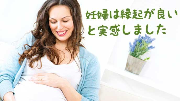 自分のお腹を撫で微笑む妊婦
