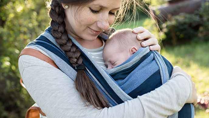赤ちゃんを抱っこして散歩する母親