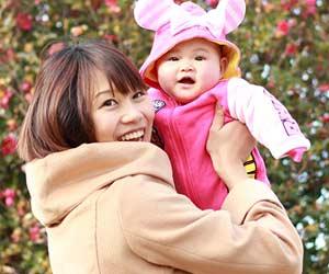 着ぐるみを着た赤ちゃんを抱っこする母親
