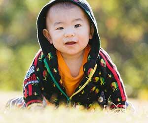 春の公園で芝生の上で遊ぶ赤ちゃん