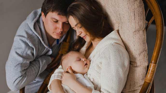 新生児を抱いた妻を見守る夫