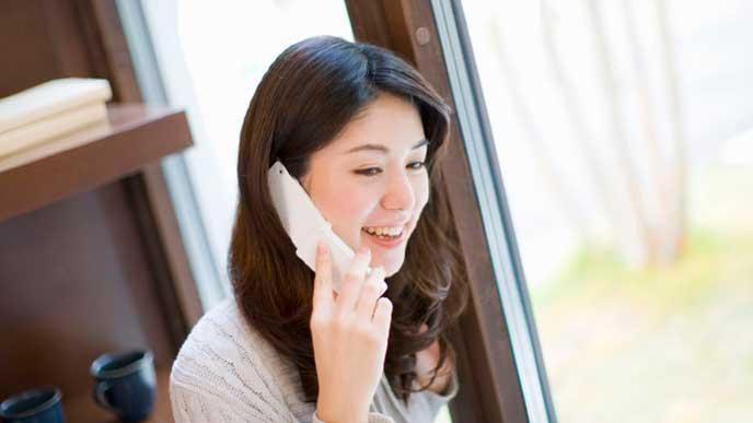 自宅のリビングで電話をする女性
