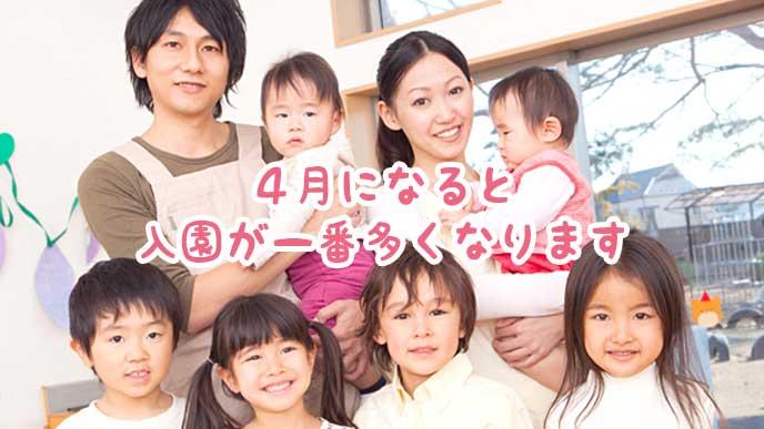赤ちゃんを抱っこしている保育園の先生と園児達