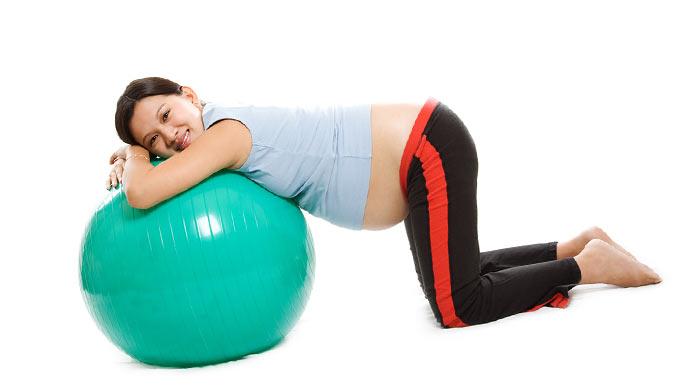 バランスボールにもたれかかる妊婦