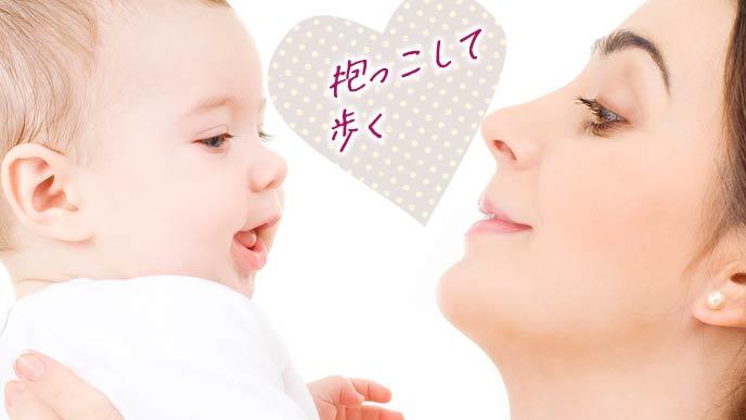 赤ちゃんを抱っこしながら歩く母親