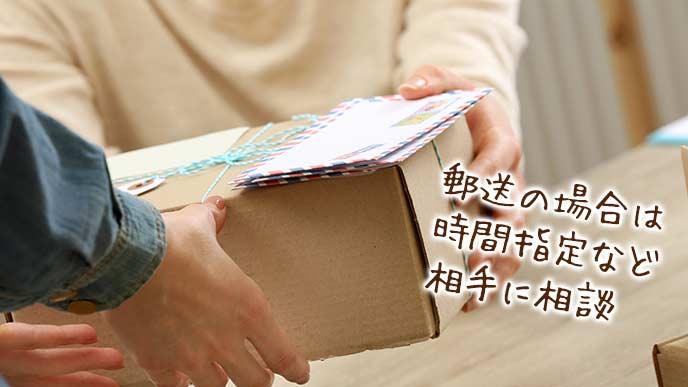 郵便局に荷物を差し出す女性
