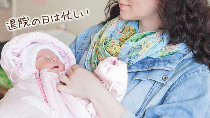 赤ちゃんを抱いて病室を出ていく母親
