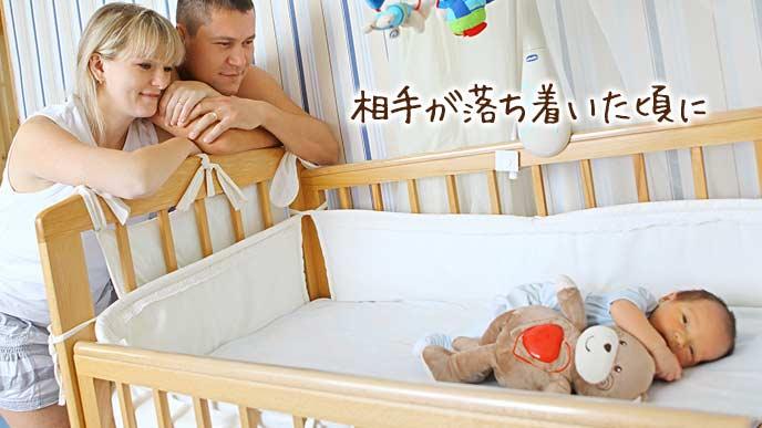 ベビーでぬいぐるみを抱く赤ちゃんを見守る両親