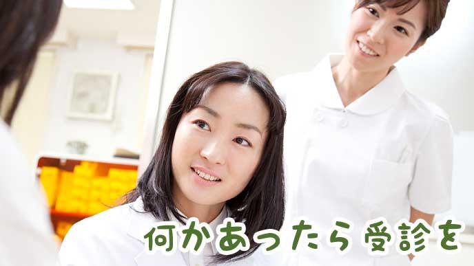 病院で妊婦の診察を行っている女医と看護師