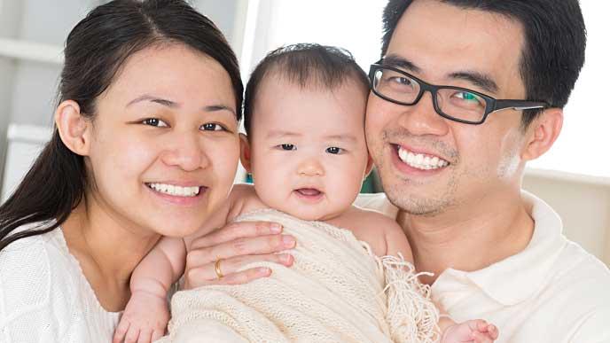 ニッコリ微笑む赤ちゃんと夫婦