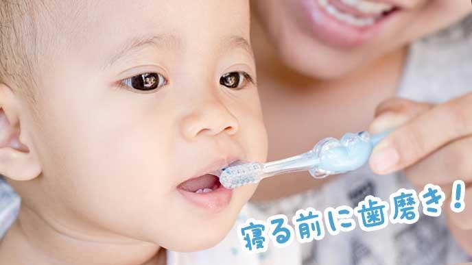 お母さんに歯磨きしてもらっている赤ちゃん
