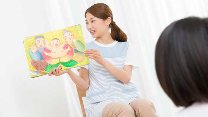 子供に桃太郎の紙芝居を読む保育士