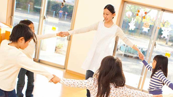 輪になって子供達と踊る保育士