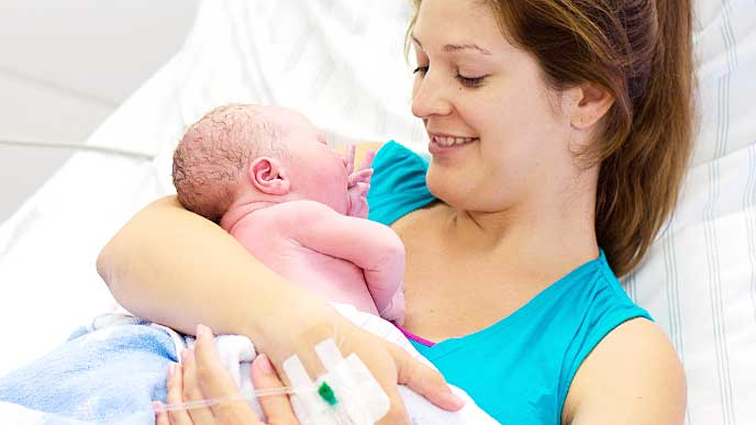 出産した赤ちゃんと触れ合い微笑む母親