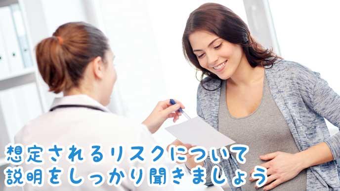 病院で医師から説明を聞いている妊婦