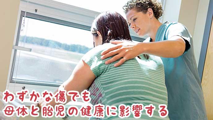 具合が悪い妊婦を看護している医師の女性