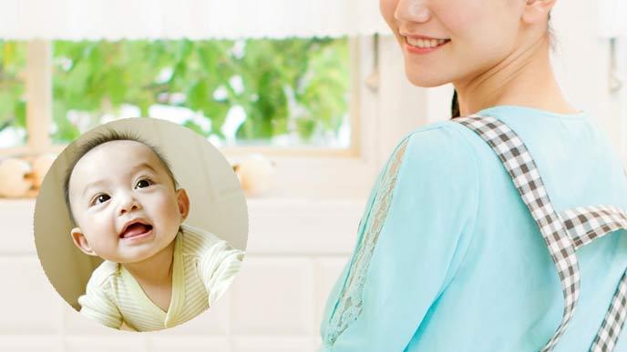 台所に立つ女性とハイハイする赤ちゃん