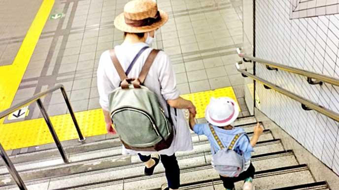 リュックを背負って駅の階段を下りる母親と赤ちゃん
