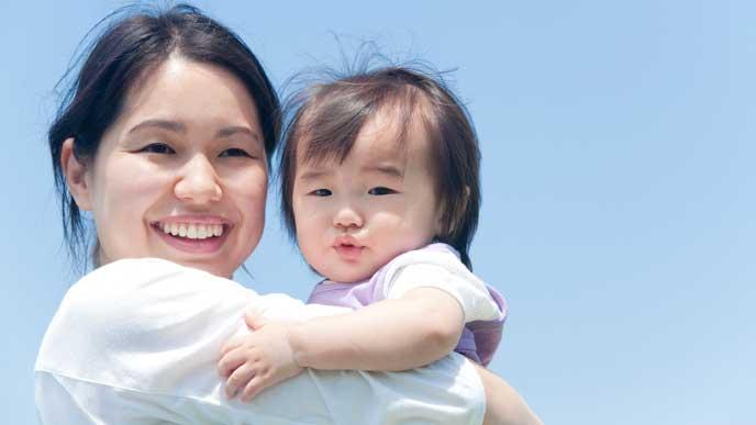赤ちゃんを縦抱きして微笑む母親