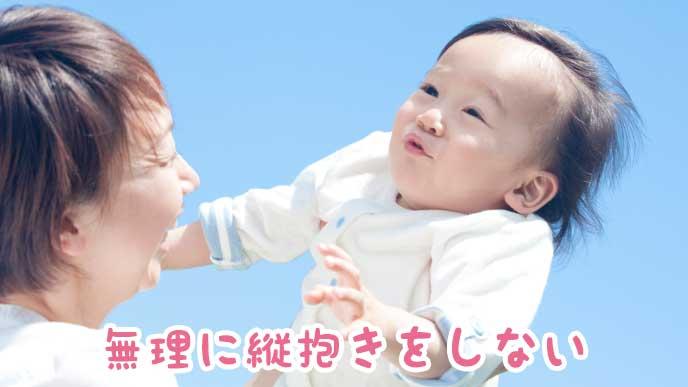 のけぞっている赤ちゃんと抱っこしようとしている母親