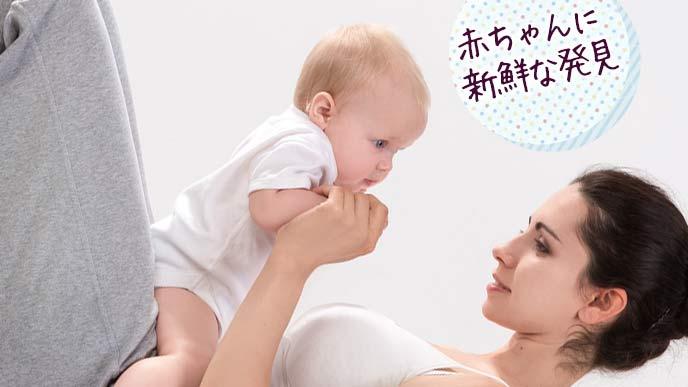 お腹の上に赤ちゃんを抱えて見つめる母親