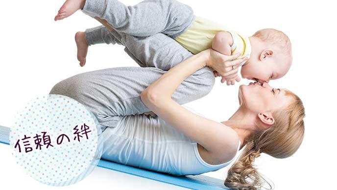 脛の上に載せた赤ちゃんにキスする母親