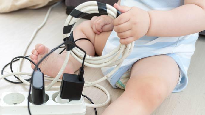 電気コードをいじる赤ちゃん