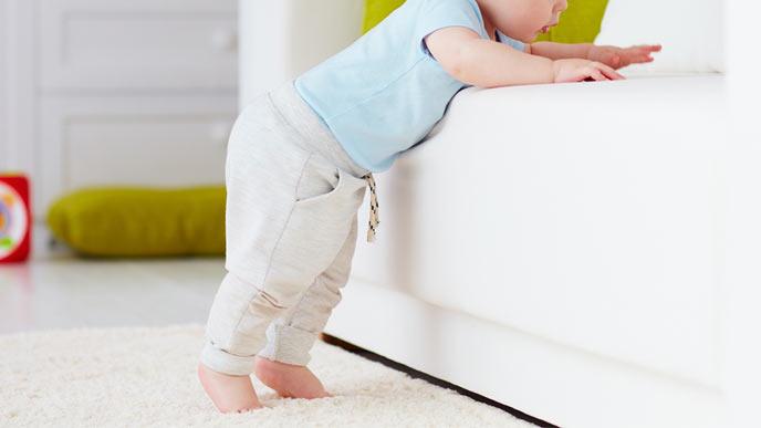 ソファに寄りかかるようにして立つ赤ちゃん