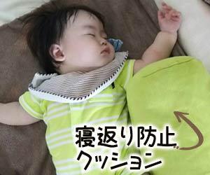寝返り防止のクッションのわきで眠る赤ちゃん