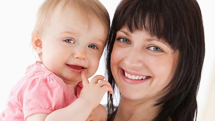 ニッコリ微笑んでいる赤ちゃんと母親の写真