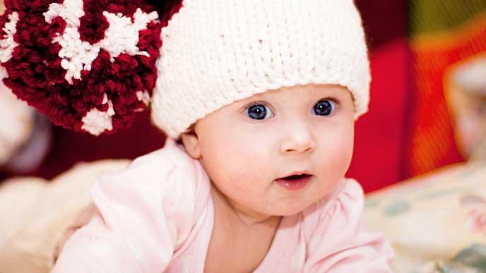 白いニット帽を被った赤ちゃんの写真